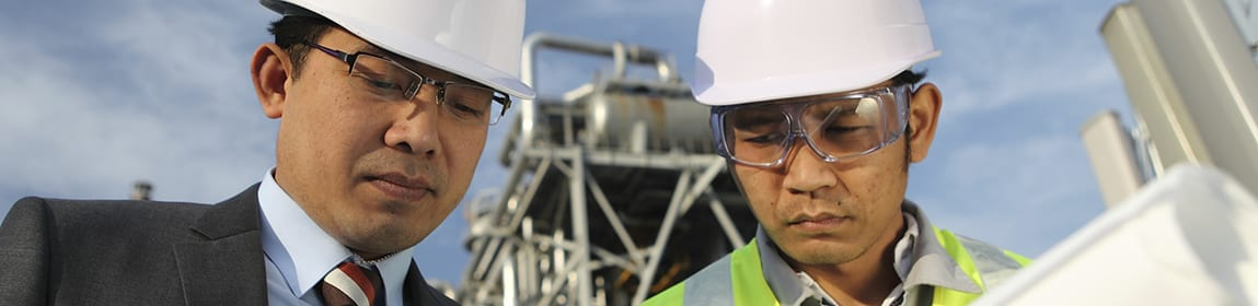 Manager and workman discussing a project in front of a refinery