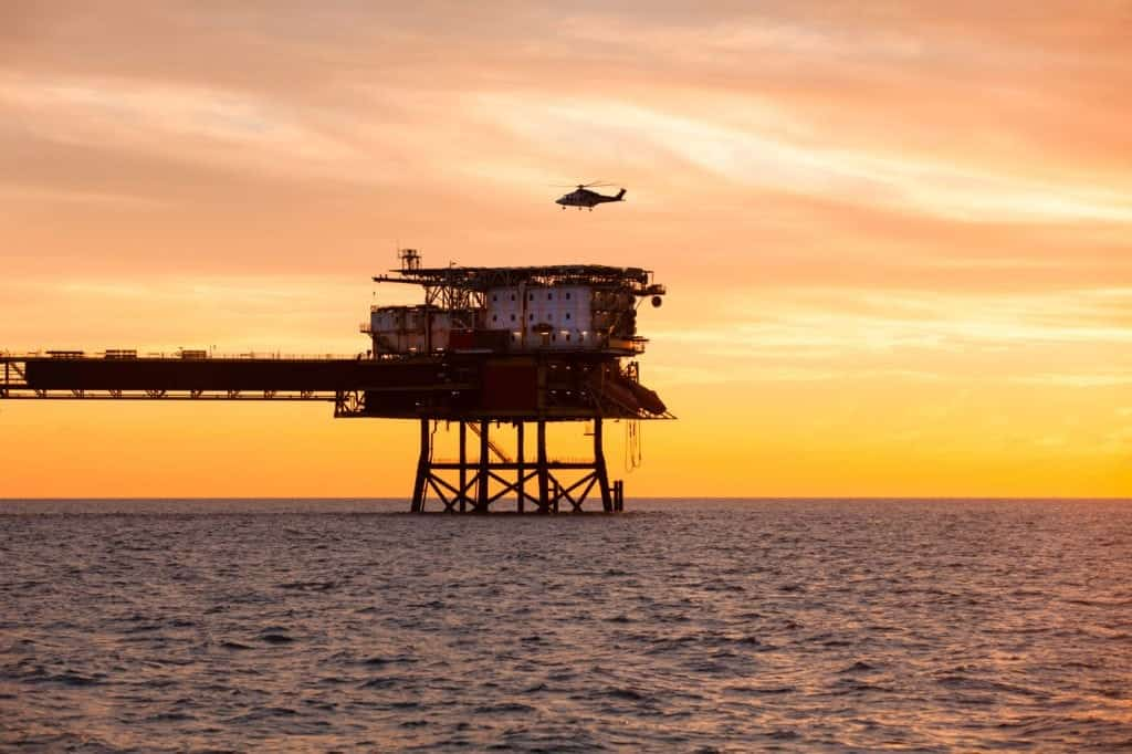 Helicopter is landing on an offshore oil installation during sunset